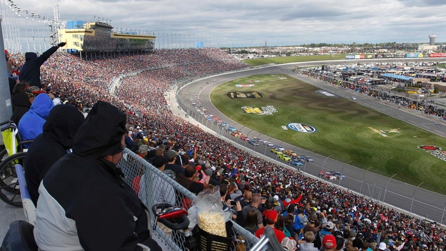 Fans watch a restart of a NASCAR Sprint Cup series auto race at Kansas Speedway in Kansas City, Kan., Sunday, Oct. 6, 2013. A crash on the first lap of the race caused the caution. (AP Photo/Colin E. Braley)