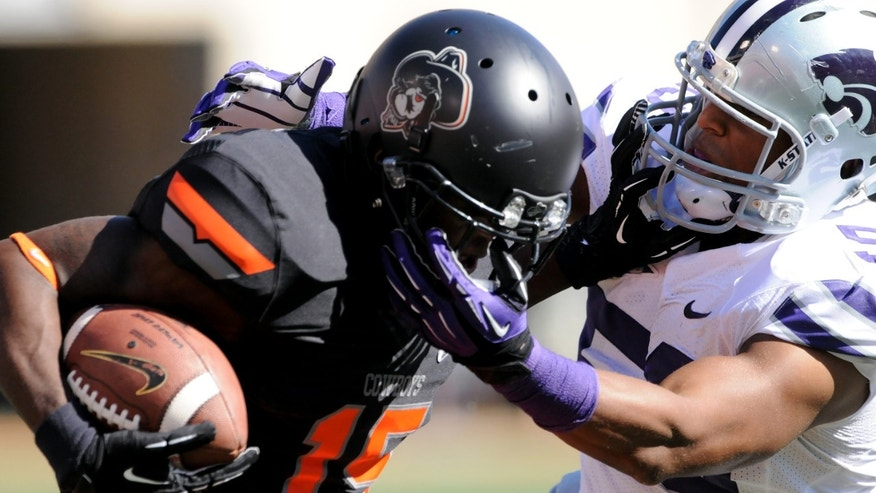 Kansas State's Blake Slaughter, right, grabs the facemask of Oklahoma State's John Goodlett, left, during the first half of an NCAA football game in Stillwater, Okla., Saturday, Oct. 5, 2013. Oklahoma State won 33-29. (AP Photo/Brody Schmidt)