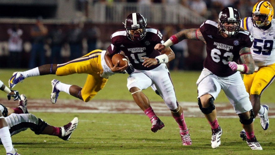 Mississippi State quarterback Dak Prescott (15) dodges an LSU defender as teammate offensive linesman Dillon Day (63) leads his run in the second half of their NCAA college football game in Starkville, Miss., Saturday, Oct. 5, 2013. No. 10 LSU won 59-26. (AP Photo/Rogelio V. Solis)