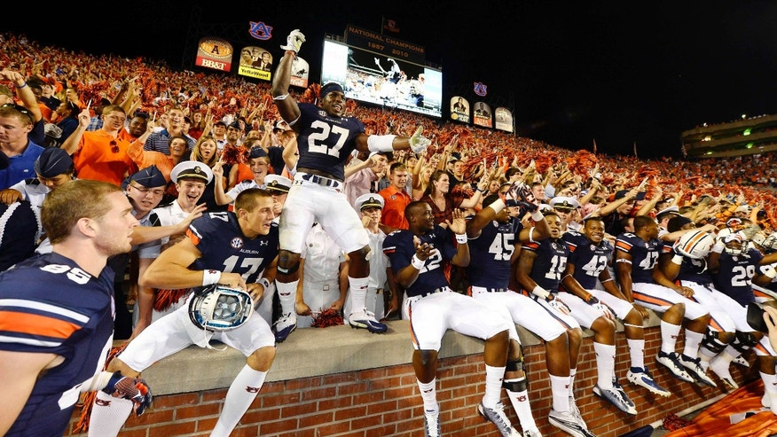 Auburn players celebrate their 30-22 win against Mississippi during an NCAA college football game on Saturday, Oct. 5, 2013, in Auburn, Ala. (AP Photo/Todd J. Van Emst)