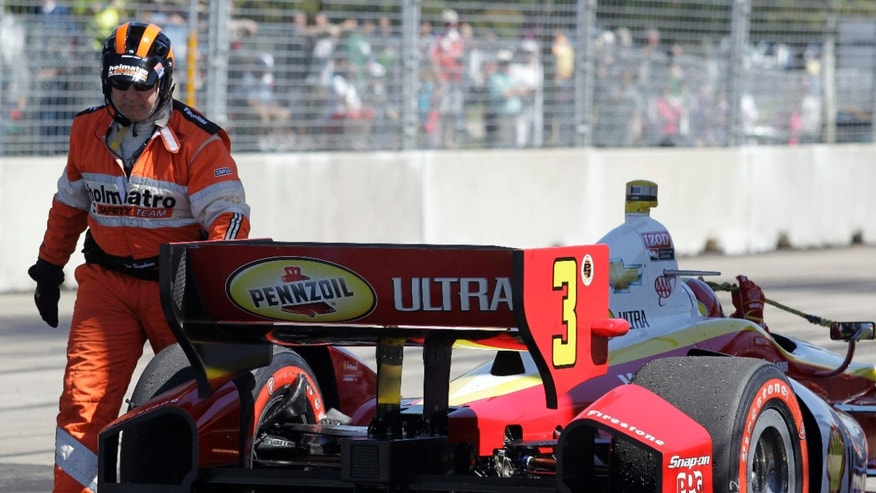Helio Castroneves, of Brazil, is helped by a member of the safety team during the second IndyCar Grand Prix of Houston auto race, Sunday, Oct. 6, 2013, in Houston. (AP Photo/Patric Schneider)