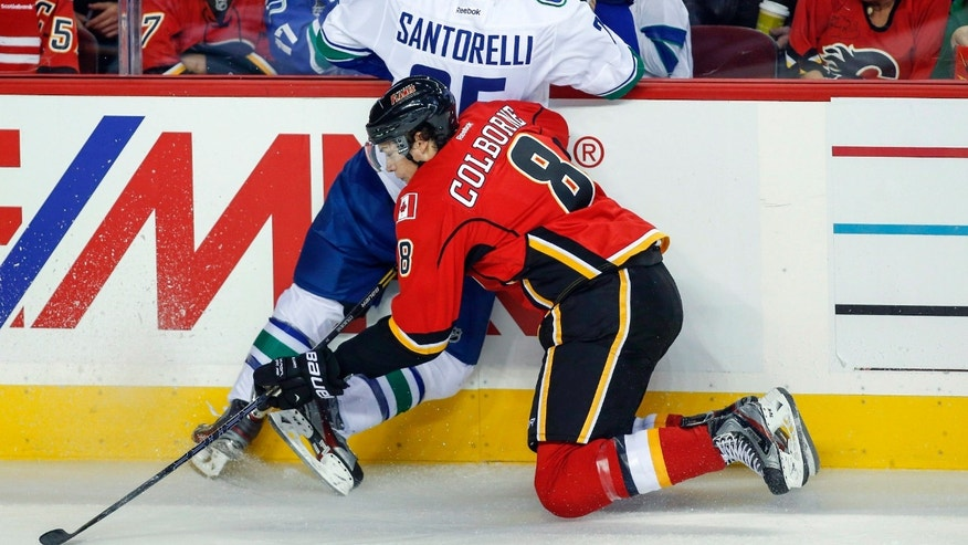 Vancouver Canucks' Mike Santorelli, left, is checked into the boards by Calgary Flames' Joe Colborne during first period NHL hockey action in Calgary, Alberta, Sunday, Oct. 6, 2013. (AP Photo/The Canadian Press, Jeff McIntosh)