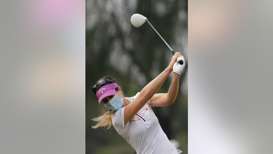 Germany's Sandra Gal, wearing a mask, tees off on the forth hole on a hazy day during the final round of the Reignwood LPGA Classic golf tournament at Pine Valley Golf Club on the outskirts of Beijing, China, Sunday, Oct. 6, 2013. Fog and pollution descended on northern China on Sunday, forcing international golf and tennis players to play in hazardous smog and leading to flight cancellations and road closures as millions of Chinese headed home from a national holiday. (AP Photo/Alexander F. Yuan)