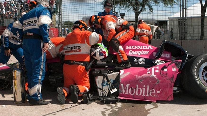 Oct. 6, 2013: Safety team members work to remove Dario Franchitti, of Scotland, from his car after a crash during the second IndyCar Grand Prix of Houston auto race.