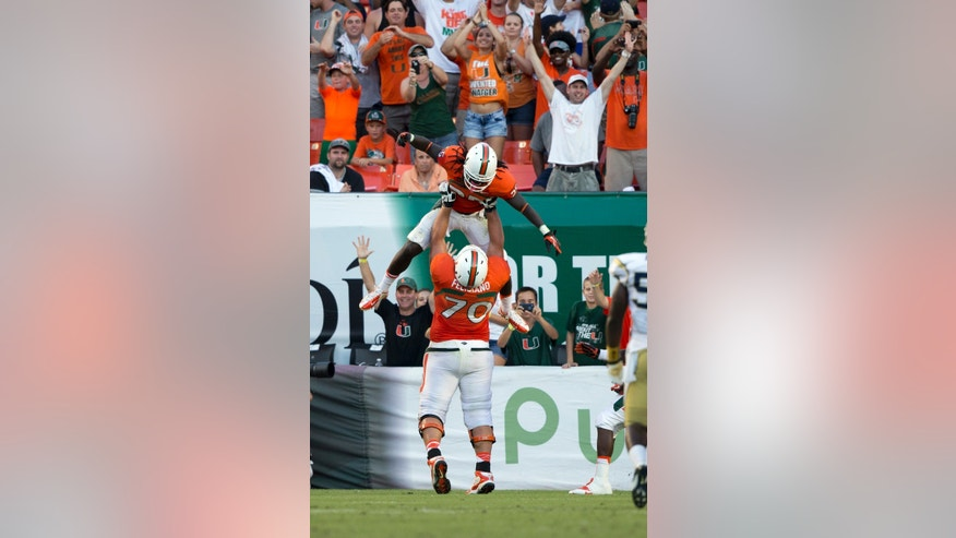 Miami players Jon Feliciano (70) and Dallas Crawford celebrate after Crawford scored a touchdown against Georgia Tech during the second half of an NCAA college football game in Miami Gardens, Fla., Saturday, Oct. 5, 2013. Miami won 45-30. (AP Photo/J Pat Carter)
