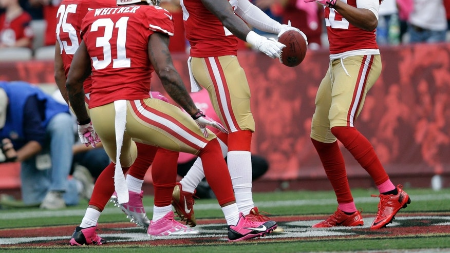 San Francisco 49ers cornerback Tramaine Brock (26) is congratulated by Eric Reid (35), Donte Whitner (31) and Carlos Rogers (22) after scoring a touchdown in the first quarter an NFL football game against the Houston Texans in San Francisco, Sunday, Oct. 6, 2013. (AP Photo/Marcio Jose Sanchez)