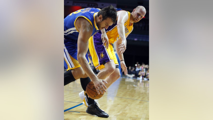 Golden State Warriors center Andrew Bogut, left, of Australia, steals the ball from Los Angeles Lakers center Chris Kaman in the first quarter during an NBA basketball preseason game Saturday, Oct. 5, 2013, in Ontario, Calif. (AP Photo/Alex Gallardo)