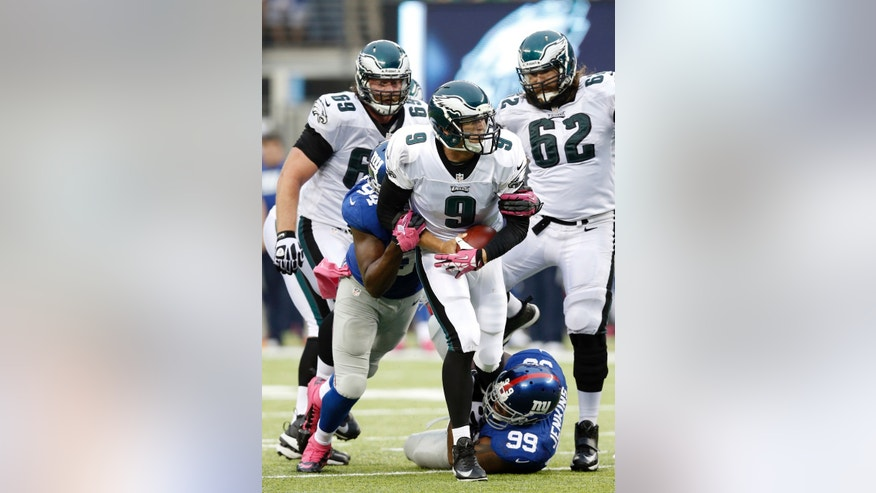 New York Giants' Cullen Jenkins (99) and Mathias Kiwanuka (94) sack Philadelphia Eagles quarterback Nick Foles (9) during the second half of an NFL football game on Sunday, Oct. 6, 2013, in East Rutherford, N.J. (AP Photo/Kathy Willens)