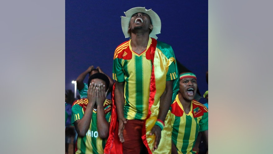 FILE- in this photo taken Tuesday, Jan. 29, 2013, Ethiopians, resident in South Africa, react as they watch their team's African Cup of Nations Group C match against Nigeria, on a big screen on the beach in Durban, South Africa. After falling off the football map for thre decades Ethiopia is now just two games away from qualifying for the 2014 World Cup in Brazil.(AP Photo/Rebecca Blackwell, file)