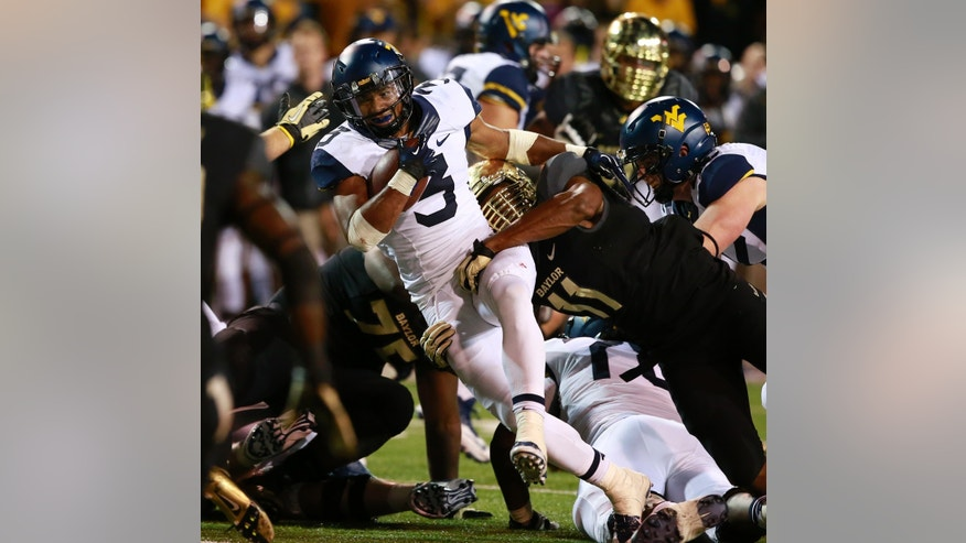West Virginia running back Charles Sims (3) is pulled down by Baylor defensive end Terrance Lloyd (11), right, during the second half  of an NCAA college football game on Saturday, Oct.  5, 2013, in Waco, Texas. (AP Photo/Jose Yau)