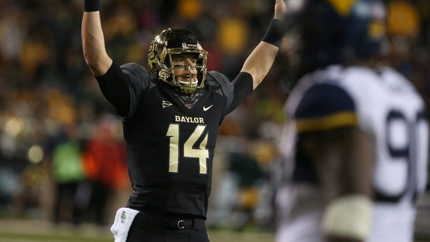 Baylor quarterback Bryce Petty (14), holds up his hands after a touchdown against West Virginia during the first half of an NCAA college football game on Saturday, Oct.  5, 2013, in Waco, Texas.  (AP Photo/Rod Aydelotte)