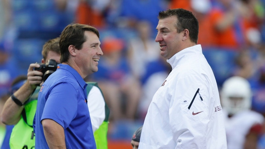 Florida head coach Will Muschamp, left, greets Arkansas head coach Bret Bielema at midfield before an NCAA college football game in Gainesville, Fla., Saturday, Oct. 5, 2013.(AP Photo/John Raoux)