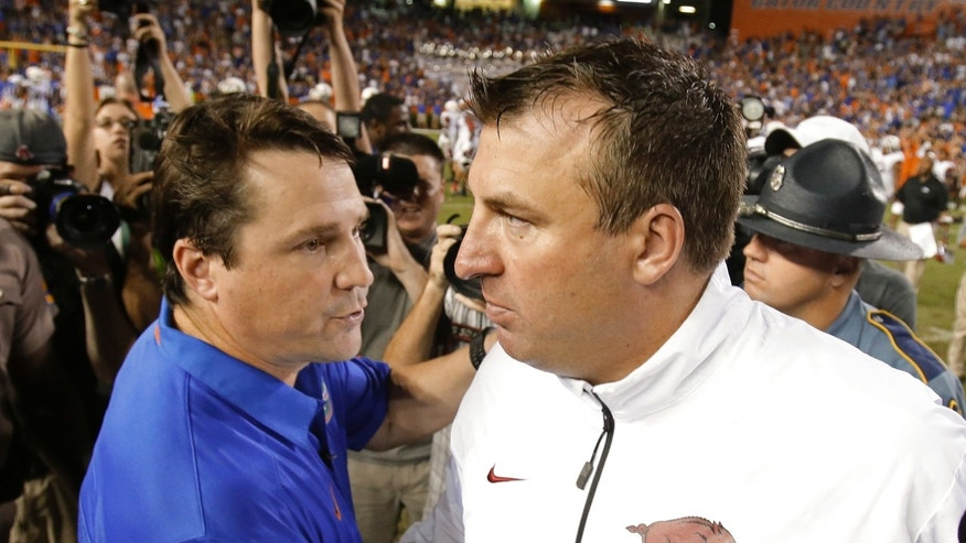 Florida coach Will Muschamp, left, greets Arkansas coach Bret Bielema on the field after an NCAA college football game in Gainesville, Fla., Saturday, Oct. 5, 2013. Florida defeated Arkansas 30-10. (AP Photo/John Raoux)