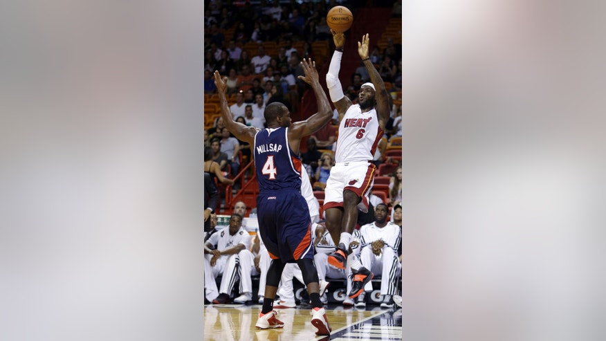 Miami Heat's LeBron James (6) prepares to pass as Atlanta Hawks' Paul Millsap (4) defends in the first quarter of an NBA preseason basketball game, Monday, Oct. 7, 2013, in Miami. (AP Photo/Alan Diaz)