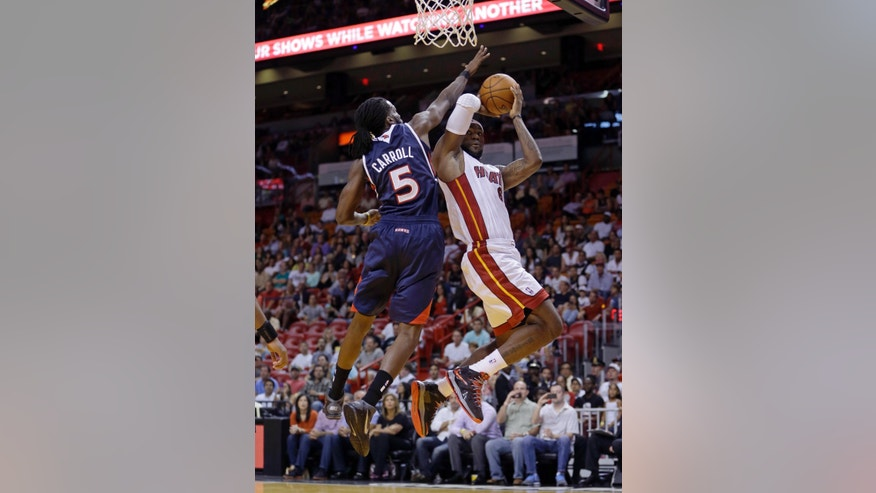 Miami Heat's LeBron James, right, prepares to shoot as Atlanta Hawks' DeMarre Carroll (5) defends in the second quarter of an NBA preseason basketball game, Monday, Oct. 7, 2013, in Miami. (AP Photo/Alan Diaz)