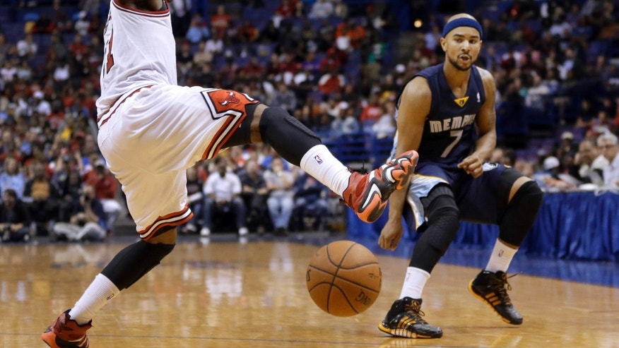 Chicago Bulls' Jimmy Butler, left, tries to block a pass by Memphis Grizzlies' Jerryd Bayless during the first half of an NBA preseason basketball game Monday, Oct. 7, 2013, in St. Louis. (AP Photo/Jeff Roberson)