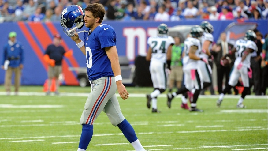 New York Giants quarterback Eli Manning reacts after throwing an interception to Philadelphia Eagles' Brandon Boykin during the second half of an NFL football game on Sunday, Oct. 6, 2013, in East Rutherford, N.J.  (AP Photo/Bill Kostroun)