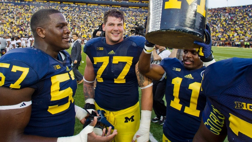 Michigan defensive end Frank Clark (57), offensive lineman Taylor Lewan (77), and cornerback Courtney Avery (11) gather around the Little Brown Jug trophy after defeating Minnesota 42-13 in an NCAA college football game, Saturday, Oct. 5, 2013, in Ann Arbor, Mich. (AP Photo/Tony Ding)