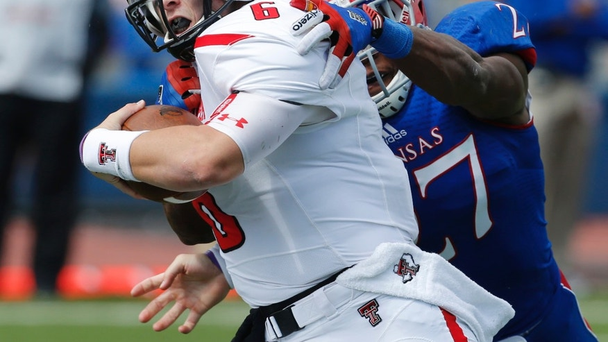 Texas Tech quarterback Baker Mayfield (6) is tackled by Kansas linebacker Victor Simmons (27) during the first half of an NCAA college football game in Lawrence, Kan., Saturday, Oct. 5, 2013. (AP Photo/Orlin Wagner)