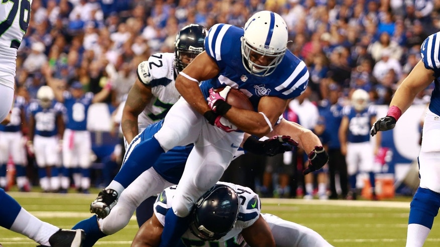 Indianapolis Colts running back Donald Brown, top, goes over Seattle Seahawks middle linebacker Bobby Wagner to score a touchdown during the second half of an NFL football game in Indianapolis, Sunday, Oct. 6, 2013. (AP Photo/Brent R. Smith)