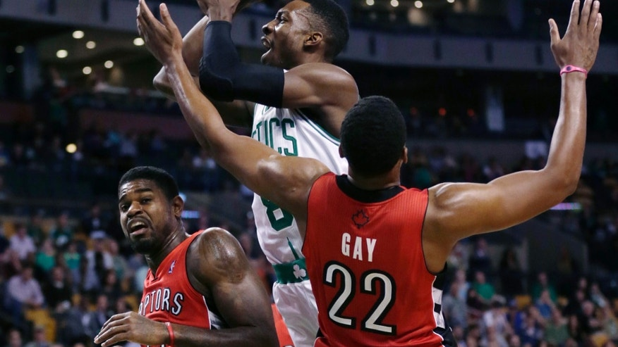 Boston Celtics forward Jeff Green, center, drives between Toronto Raptors forwards Amir Johnson, left, and Rudy Gay during the first quarter of a preseason NBA basketball game, Monday, Oct. 7, 2013, in Boston. (AP Photo/Charles Krupa)