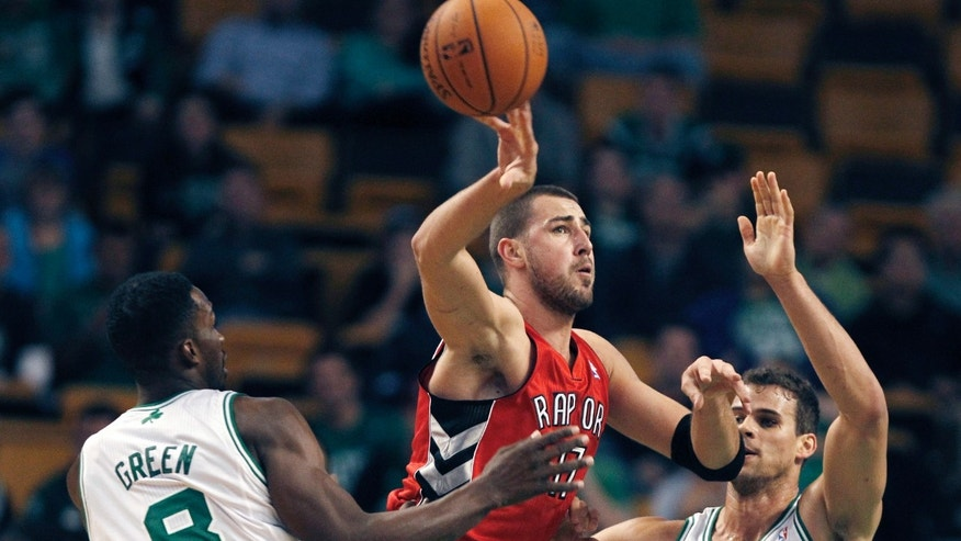 Toronto Raptors center Jonas Valanciunas (17), of Lithuania, passes as he is pressured by Boston Celtics forwards Jeff Green (8) and Kris Humphries during the first quarter of a preseason NBA basketball game, Monday, Oct. 7, 2013, in Boston. (AP Photo/Charles Krupa)