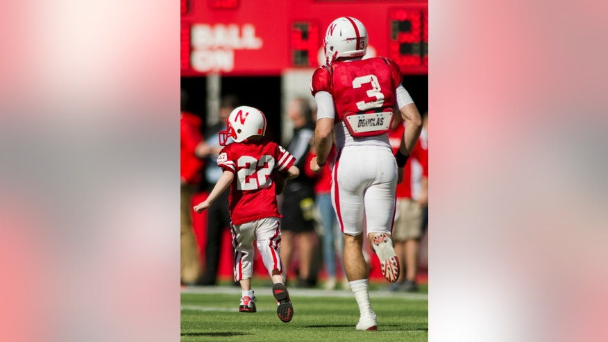 FILE - In this April 6, 2013 file photo, Nebraska's Taylor Martinez (3) guides Jack Hoffman, then 6, of Atkinson, Neb., down the field for his touchdown play during a special segment dedicated to Hoffman during the second half of the Red-White spring NCAA college football game at Memorial Stadium in Lincoln, Ne. Andy Hoffman, the father of Jack Hoffman, said Monday, Oct. 7, 2013, that his family has been thankful and cautiously excited since learning last week that Jack's brain cancer is in remission. Jack captured the hearts of Nebraska football fans when, with the help of the players, he ran for a touchdown during an intrasquad game that ended spring football practice earlier this year. The scoring scamper has been replayed on national TV and viewed nearly 8.4 million times on YouTube. (AP Photo/Lincoln Journal Star, Matt Ryerson, File) LOCAL TV OUT; KOLN-TV OUT; KGIN-TV OUT; KLKN-TV OUT