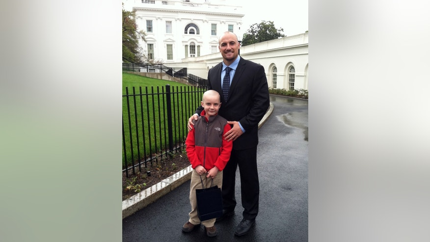 FILE - In this April 29, 2013 file photo provided by Andy Hoffman, his son Jack stands with former Nebraska football player Rex Burkhead after meeting with President Barack Obama in Washington. Andy Hoffman, the father of Jack Hoffman, said Monday, Oct. 7, 2013, that his family has been thankful and cautiously excited since learning last week that Jack's brain cancer is in remission. Jack captured the hearts of Nebraska football fans when, with the help of the players, he ran for a touchdown during an intrasquad game that ended spring football practice earlier this year. The scoring scamper has been replayed on national TV and viewed nearly 8.4 million times on YouTube. (AP Photo/Courtesy Jack Hoffman, File)