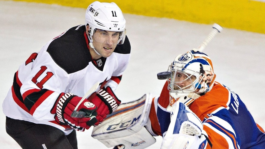 New Jersey Devils Stephen Gionta (11) chases the rebound as Edmonton Oilers goalie Jason LaBarbera (1) makes the save during the first period of an NHL hockey game Monday, Oct. 7, 2013, in Edmonton, Alberta. (AP Photo/The Canadian Press, Jason Franson)