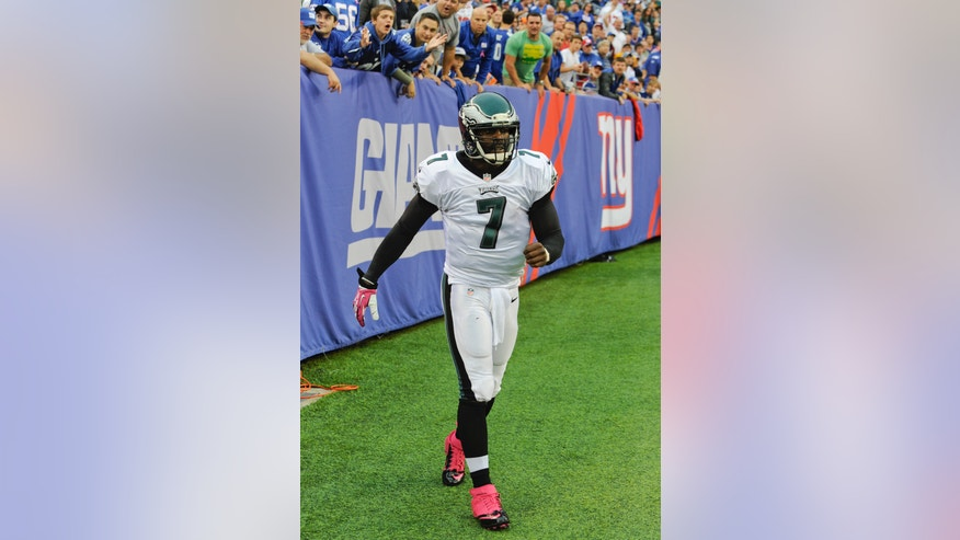 Philadelphia Eagles quarterback Michael Vick (7) walks back onto the field of play during the first half of an NFL football game against the New York Giants Sunday, Oct. 6, 2013, in East Rutherford, N.J.  (AP Photo/Bill Kostroun)