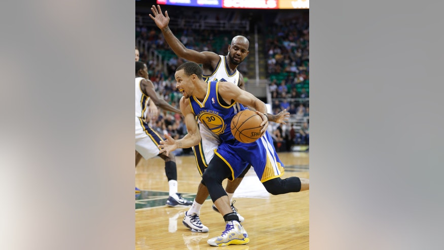 Golden State Warriors guard Stephen Curry (30) drives to the basket as Utah Jazz guard John Lucas III defends in the second quarter during an NBA preseason basketball game Tuesday, Oct. 8, 2013, in Salt Lake City. (AP Photo/Rick Bowmer)