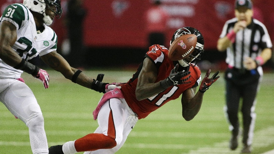 Atlanta Falcons wide receiver Julio Jones (11) vies for a thrown ball against New York Jets cornerback Antonio Cromartie (31) during the second half of an NFL football game, Monday, Oct. 7, 2013, in Atlanta. (AP Photo/John Bazemore)
