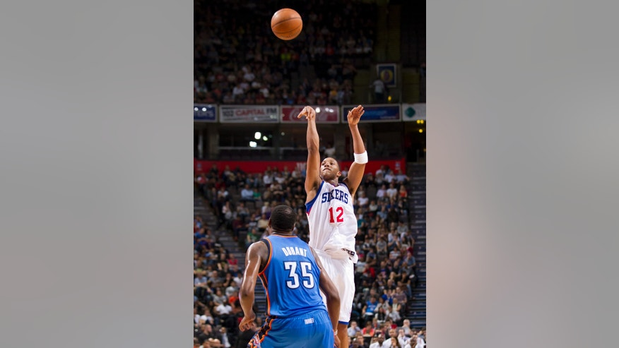 Philadelphia 76ers' Evan Turner, right, takes a shot as Oklahoma City Thunder's Kevin Durnat looks on during their NBA preseason basketball game at the Phones4 u Arena in Manchester, England, Tuesday, Oct. 8, 2013. (AP Photo/Jon Super)