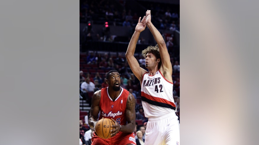 Los Angeles Clippers center DeAndre Jordan, left, looks to shoot as Portland Trail Blazers center Robin Lopez defends during the first half of an NBA preseason basketball game in Portland, Ore., Monday, Oct. 7, 2013. (AP Photo/Don Ryan)