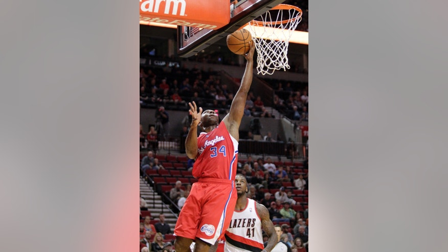 Los Angeles Clippers guard Willie Green, left, goes to the basekt past Portland Trail Blazers forward Thomas Robinson during the first half of an NBA preseason basketball game in Portland, Ore., Monday, Oct. 7, 2013. (AP Photo/Don Ryan)