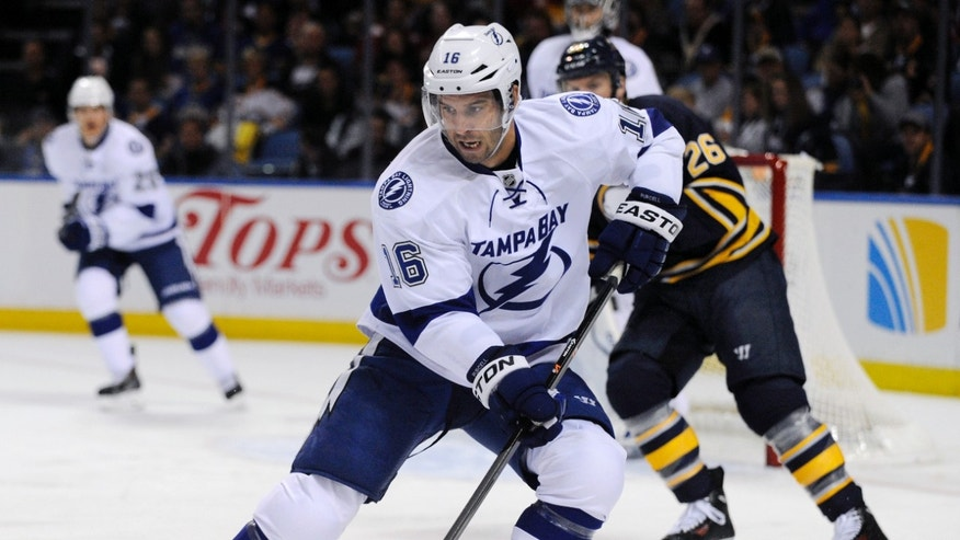 Tampa Bay Lightning right winger Teddy Purcell skates for the puck as Buffalo Sabres left winger Thomas Vanek (26) gives chase during the first period of an NHL hockey game in Buffalo, N.Y., Tuesday, Oct. 8, 2013. (AP Photo/Gary Wiepert)