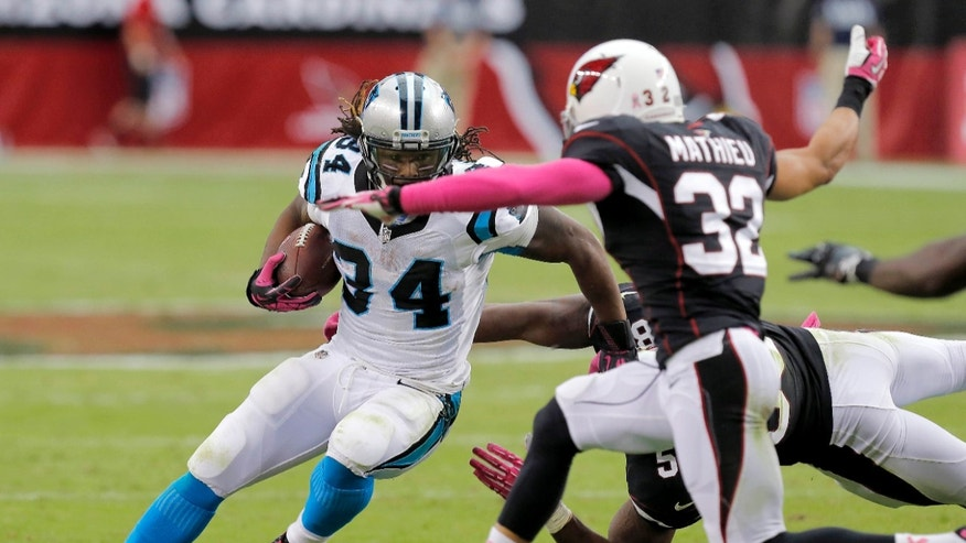 Carolina Panthers running back DeAngelo Williams (34) tries to escape Arizona Cardinals free safety Tyrann Mathieu (32) and Daryl Washington during the second half of a NFL football game, Sunday, Oct. 6, 2013, in Glendale, Ariz. (AP Photo/Ross D. Franklin)