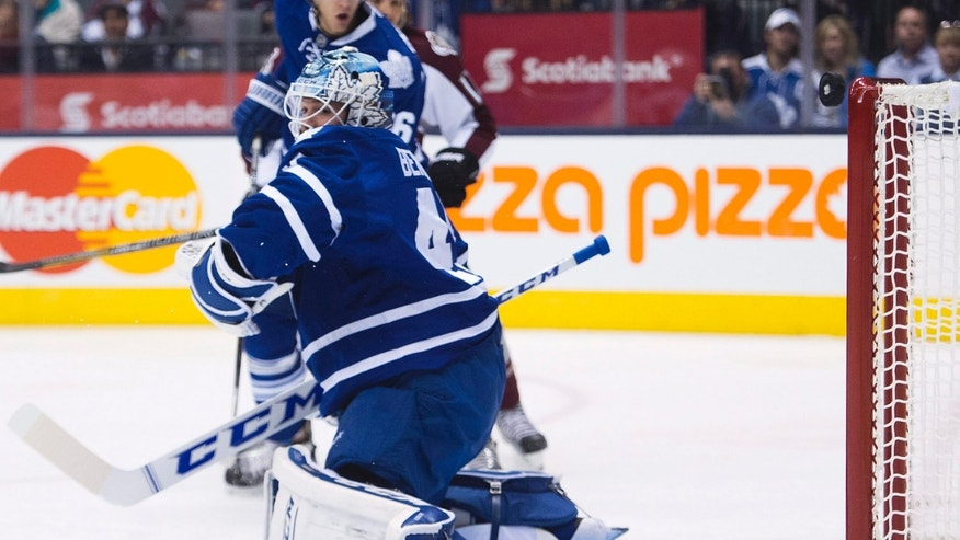 Toronto Maple Leafs goalie Jonathan Bernier looks back as the puck rings off the crossbar on a Colorado Avalanche shot during the first period of an NHL hockey game in Toronto on Tuesday, Oct. 8, 2013. (AP Photo/The Canadian Press, Nathan Denette)
