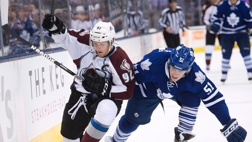 Toronto Maple Leafs defenseman Jake Gardiner, right, and Colorado Avalanche forward Gabriel Landeskog, left, chase the puck after a check by Gardiner during the first period of an NHL hockey game in Toronto on Tuesday, Oct. 8, 2013. (AP Photo/The Canadian Press, Nathan Denette)