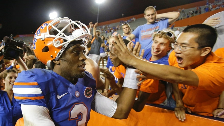Florida quarterback Tyler Murphy (3) high-fives fans after Florida defeated Arkansas 30-10 in an NCAA college football game in Gainesville, Fla., Saturday, Oct. 5, 2013. (AP Photo/John Raoux)