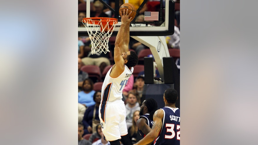Charlotte Bobcats forward Jeffery Taylor, left, drives to the basket during the first half of a preseason NBA basketball game against Atlanta Hawks in Asheville, N.C., Tuesday, Oct. 8, 2013. (AP Photo/Adam Jennings)