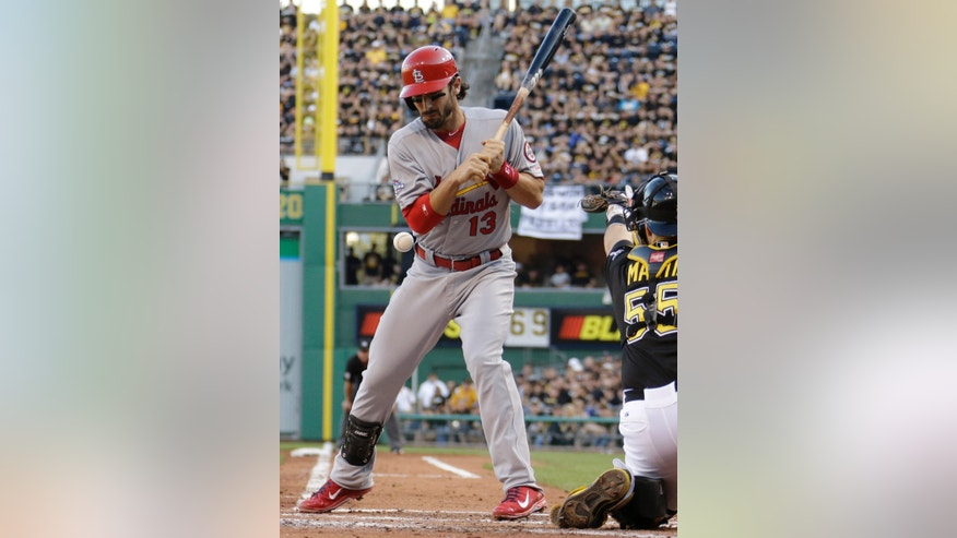 St. Louis Cardinals' Matt Carpenter (13) is hit by a pitch as Pittsburgh Pirates catcher Russell Martin reaches for it in the third inning of Game 3 of a National League division baseball series on Sunday, Oct. 6, 2013 in Pittsburgh. (AP Photo/Gene J. Puskar)