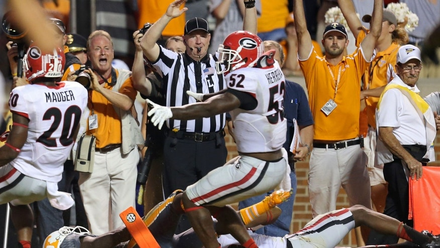 Tennessee's Alton Howard, bottom left, falls into the endzone after he fumbled the ball for a turnover as Georgia's Amarlo Herrera (52) contents the original call as a touchdown in overtime of an NCAA college football game in Knoxville, Tenn., Oct. 5, 2013. (AP Photo/Atlanta Journal-Constitution, Jason Getz)