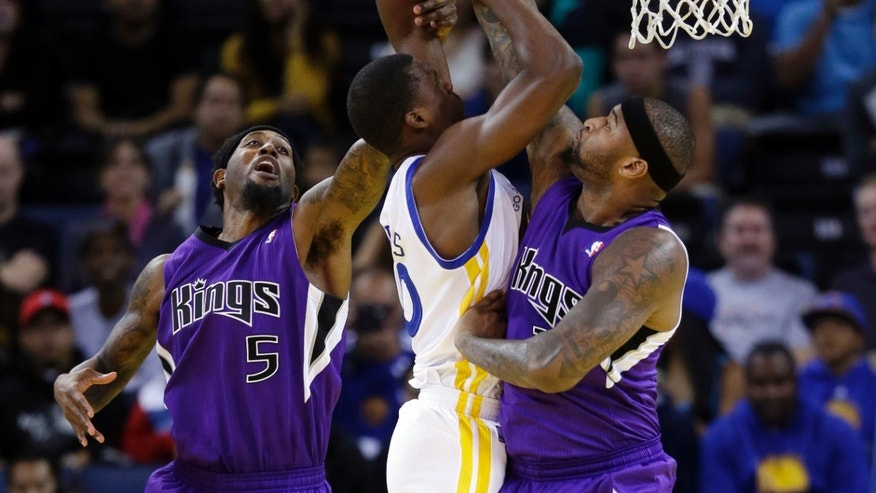 Sacramento Kings' DeMarcus Cousins, right, blocks a shot by Golden State Warriors' Harrison Barnes, center, with help from John Salmons (5) during the first half of an NBA preseason basketball game Monday, Oct. 7, 2013, in Oakland, Calif. (AP Photo/Marcio Jose Sanchez)