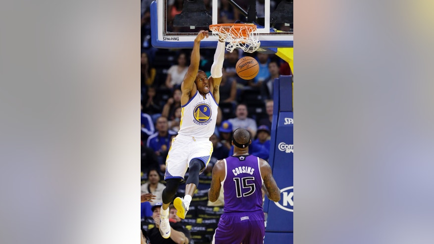 Golden State Warriors' Andre Iguodala (9) dunks in front of Sacramento Kings' DeMarcus Cousins (15) during the first half of an NBA preseason basketball game Monday, Oct. 7, 2013, in Oakland, Calif. (AP Photo/Marcio Jose Sanchez)