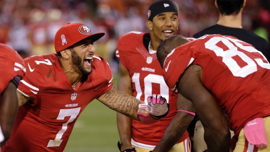 San Francisco 49ers quarterback Colin Kaepernick (7) and tight end Vernon Davis, right, laugh after winning their game 34-3 against the Houston Texans during an NFL football game in San Francisco, Sunday, Oct. 6, 2013. (AP Photo/Marcio Jose Sanchez)