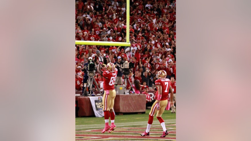 San Francisco 49ers tight end Vernon Davis, left, shoots the football over the goal post like a basketball after he scored a touchdown as teammate Colin Kaepernick, right, watches in the second half of an NFL football game against the Houston Texans in San Francisco, Sunday, Oct. 6, 2013. (AP Photo/Beck Diefenbach)