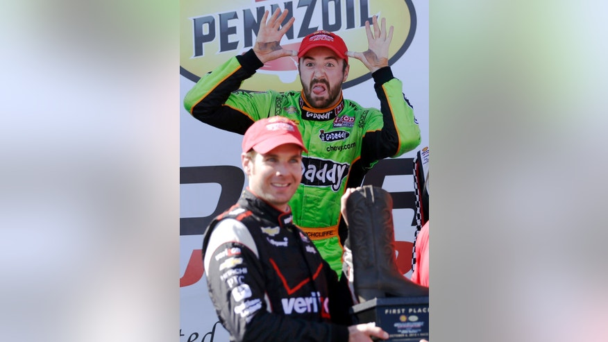 Third place finisher James Hinchcliffe, rear, of Canada, makes a face as winner Will Power, front, of Australia, is presented the winners trophy during the second IndyCar Grand Prix of Houston auto race, Sunday, Oct. 6, 2013, in Houston. (AP Photo/David J. Phillip)