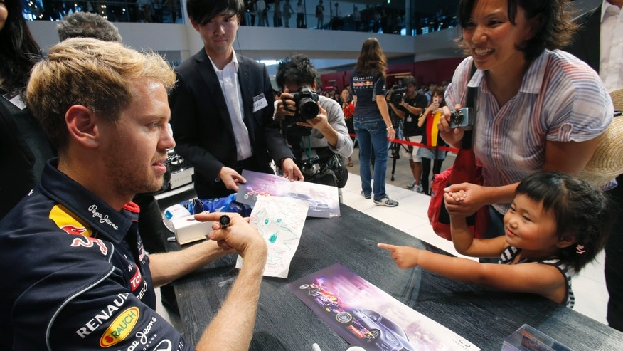 Red Bull driver Sebastian Vettel of Germany chats with his young fan as he gives her his autograph during an event at the Nissan Motor Co.'s global headquarters in Yokohama, southwest of Tokyo, Wednesday, Oct. 9, 2013. Vettel is in Japan for Sunday's Japan Grand Prix race in Suzuka, western Japan. (AP Photo/Shizuo Kambayashi)