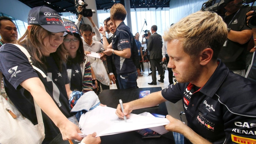 Red Bull driver Sebastian Vettel of Germany, right, gives his autograph to his fan during an event at the Nissan Motor Co.'s global headquarters in Yokohama, southwest of Tokyo, Wednesday, Oct. 9, 2013. Vettel is in Japan for the Japanese Formula One race in Suzuka, western Japan, on Sunday. (AP Photo/Shizuo Kambayashi)